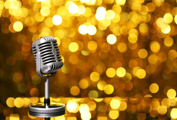 Silver microphone on orange background
