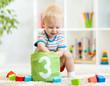 kid boy playing wooden block toys