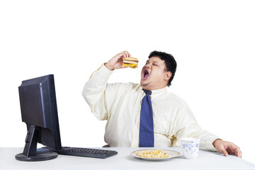 Hungry businessman eating fast food