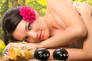 beautiful brunette woman lying down in outdoor spa