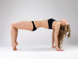 Flexible pilates trainer exercising in studio