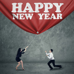 Two business person drag new year banner