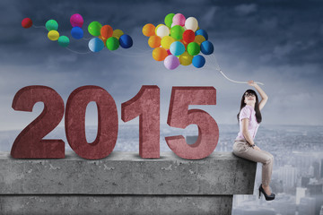 Woman with balloons and number 2015