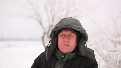 Winter time . Adult man in  hood  look and smile .Portrait