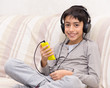 young boy listening music with smart phone and headphone