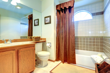 Bathroom with tile wall trim and arch window