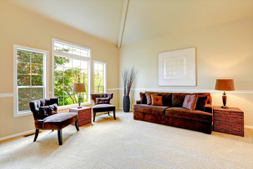 Bright ivory living room with high vaulted ceiling and french wi