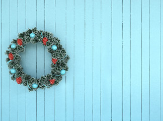 Green wreath with blue and red bow on antique aqua rustic wood