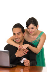 young attractive happy couple in front of computer buying online