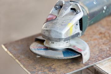 Angle grinder tool at metal sheet