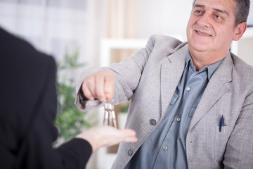senior businessman handover keys to man
