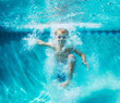 Leinwandbild Motiv Young Boy Diving Underwater in Swimming Pool
