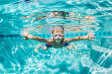 Young Boy Diving Underwater in Swimming Pool