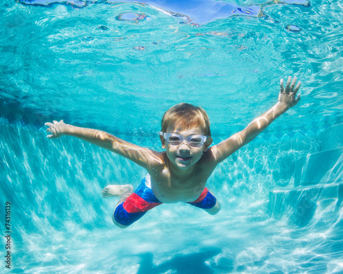 Tuinposter Duiken Young Boy Diving Underwater in Swimming Pool