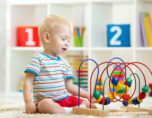 funny toddler boy playing with educational toy indoor