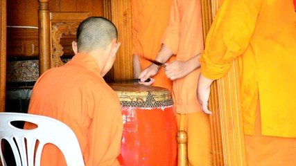 Young monk hitting the largest drum for pray in the evening