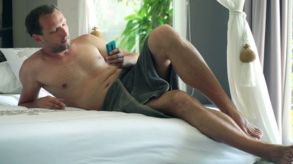 Man texting on smartphone while lying on bed