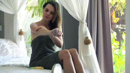 Pretty woman applying lotion moisturizer on hands in bathroom