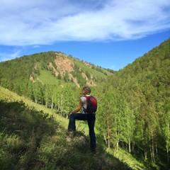 Молодая девушка с рюкзаком на прогулке в горах