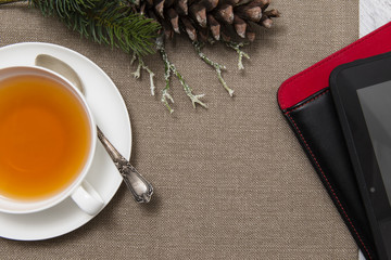Cup of tea, notepad and Christmas decoration on table cloth