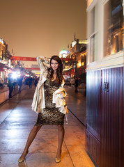 Fashion portrait of young woman on city background.