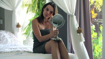 Attractive woman applying concealer on her eyelid in bedroom