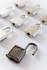 rows of padlocks on white background - open lock
