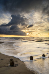 Beautiful vibrant seascape at sunset image with dramatic sky and