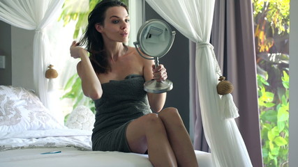 Woman checking her face in the mirror in bedroom