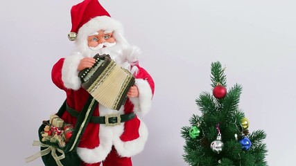 Santa playing the accordion near  Christmas tree