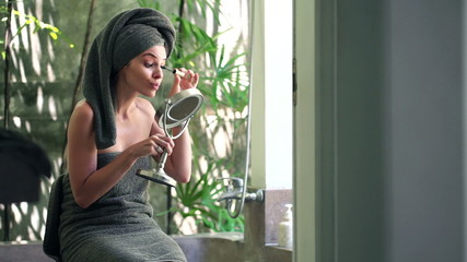 Woman applying mascara in front of the mirror in bathroom