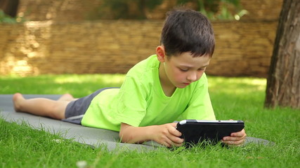 little beautiful boy plays the tablet in the park, dolly 1