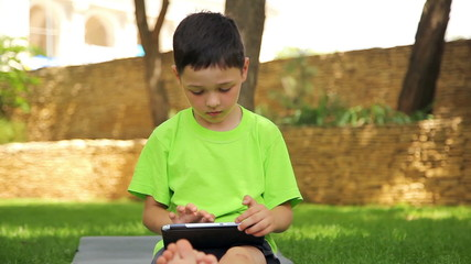 little boy plays the tablet in the park, dolly 5