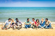 Group of multiracial best friends sitting and talking at beach