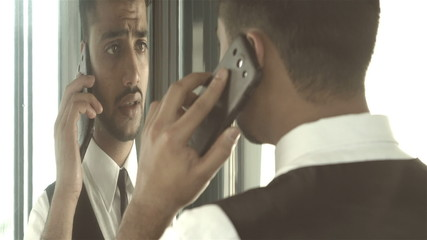 The indian businessman phone near the curved round mirror