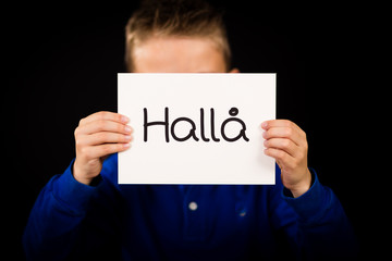 Child holding sign with Swedish word Halla - Hello