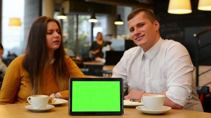 tablet green screen - happy couple smiles to camera in cafe