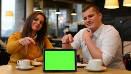 tablet green screen - happy couple smiles and point at tablet