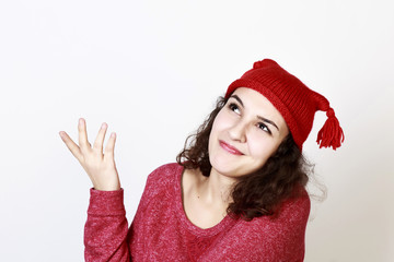 Curly young woman imagining dressed with red Christmas hat, isol