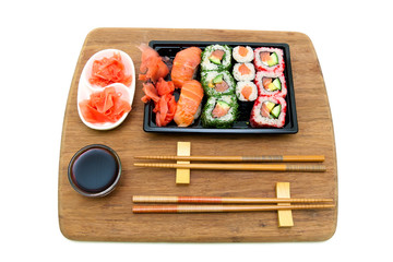 rolls and sushi on a bamboo board isolated on white background