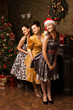 Portrait of  three young woman posing near decorated Christmas t