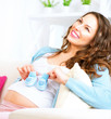 Pregnant happy woman holding blue baby shoes in her hands