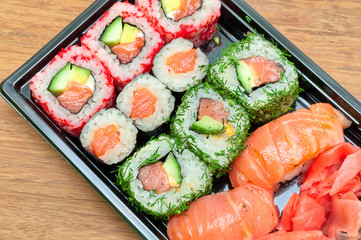 sushi, rolls and pickled ginger on a bamboo board close-up