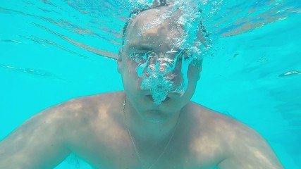 man makes bubbles under water in the pool