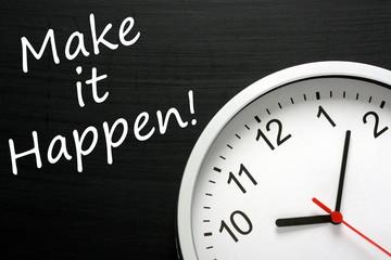 Make it Happen written on a blackboard next to a  wall clock