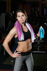 Fit smiling woman standing in gym