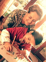 Abuela viendo a su nieta dibujar