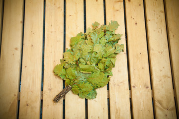 oak broom on wooden boards for baths and saunas