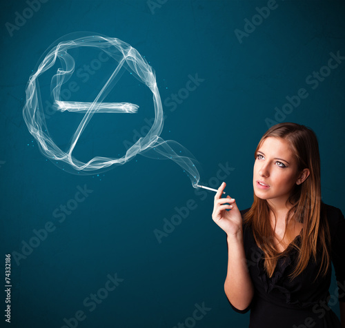 Young lady smoking unhealthy cigarette with no smoking sign - 74332186