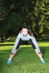 Smiling woman stretching in the park